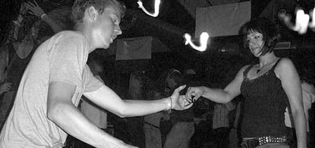 Man and Woman dance Lindy Hop at a Swing Club